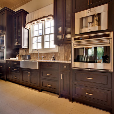 Example of a mid-sized arts and crafts l-shaped ceramic tile eat-in kitchen design in Charlotte with dark wood cabinets, granite countertops, stainless steel appliances, an island, a farmhouse sink, recessed-panel cabinets, brown backsplash and matchstick tile backsplash