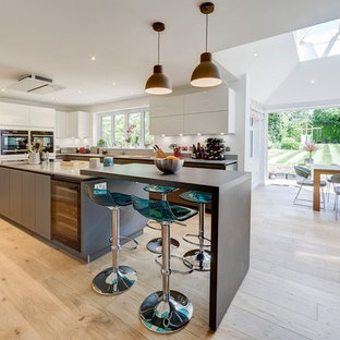 This is an example of a large contemporary kitchen/diner in London with flat-panel cabinets, light hardwood flooring, beige floors, white cabinets and stainless steel appliances.