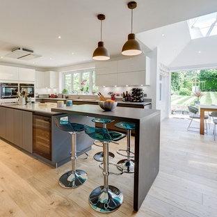 Cette image montre une grande cuisine américaine design avec un placard à porte plane, un sol en bois clair, un sol beige, des portes de placard blanches et un électroménager en acier inoxydable.