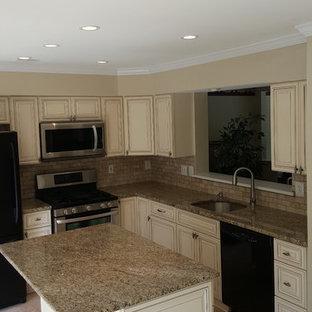 ワシントンD.C.の中サイズのシャビーシック調のおしゃれなキッチン (ベージュのキャビネット、御影石カウンター、ベージュキッチンパネル、石タイルのキッチンパネル、黒い調理設備、磁器タイルの床) の写真