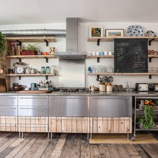 This is an example of an urban single-wall kitchen in London with light wood cabinets, concrete worktops, metallic splashback, stainless steel appliances, medium hardwood flooring, no island and grey worktops.