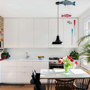 This is an example of a small scandi l-shaped kitchen/diner in London with flat-panel cabinets, white cabinets, stainless steel appliances, no island, white worktops, an integrated sink, white splashback and medium hardwood flooring.