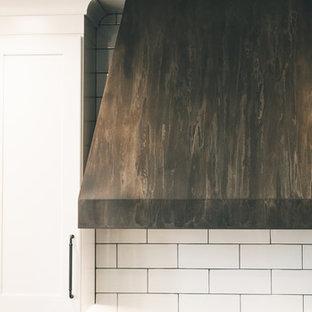Idéer för ett stort lantligt svart u-kök, med en rustik diskho, skåp i shakerstil, vita skåp, bänkskiva i kvarts, vitt stänkskydd, stänkskydd i tunnelbanekakel, rostfria vitvaror och svart golv