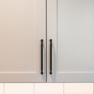 シアトルの大きいカントリー風おしゃれなコの字型キッチン (エプロンフロントシンク、シェーカースタイル扉のキャビネット、白いキャビネット、クオーツストーンカウンター、白いキッチンパネル、サブウェイタイルのキッチンパネル、シルバーの調理設備の、黒い床、黒いキッチンカウンター) の写真