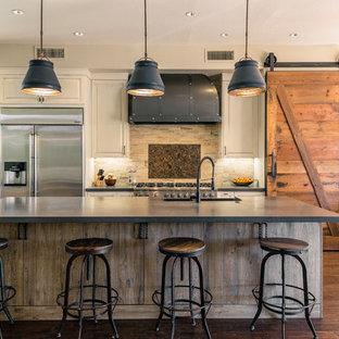 Idee per una cucina country con lavello sottopiano, ante con bugna sagomata, ante beige, elettrodomestici in acciaio inossidabile, parquet scuro e isola