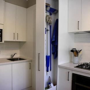 メルボルンの中サイズのコンテンポラリースタイルのおしゃれなキッチン (フラットパネル扉のキャビネット、白いキャビネット、クオーツストーンカウンター、白いキッチンパネル、セラミックタイルのキッチンパネル、シルバーの調理設備の、磁器タイルの床、シングルシンク、ベージュの床) の写真