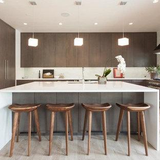 Ejemplo de cocina comedor en U, moderna, grande, con armarios con paneles lisos, electrodomésticos de acero inoxidable, suelo de madera clara, una isla, puertas de armario marrones, salpicadero azul y suelo marrón