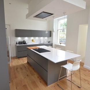 Bild på ett mellanstort funkis kök, med en dubbel diskho, släta luckor, grå skåp, bänkskiva i kalksten, svart stänkskydd, stänkskydd i marmor, svarta vitvaror, mörkt trägolv, en köksö och brunt golv
