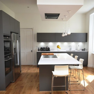 Photo of a mid-sized contemporary u-shaped eat-in kitchen in Glasgow with a double-bowl sink, flat-panel cabinets, grey cabinets, limestone benchtops, black splashback, marble splashback, black appliances, dark hardwood floors, with island and brown floor.