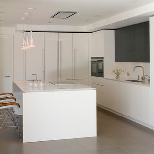 Photo of a large contemporary l-shaped kitchen/diner in London with flat-panel cabinets, white cabinets, quartz worktops, white splashback, glass sheet splashback, integrated appliances, ceramic flooring, an island, grey floors, white worktops and a submerged sink.