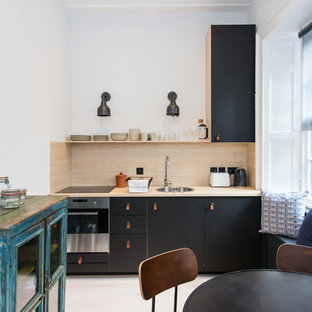 Design ideas for a scandi single-wall kitchen/diner in Edinburgh with a single-bowl sink, flat-panel cabinets, black cabinets, wood worktops, wood splashback, stainless steel appliances, light hardwood flooring and beige floors.