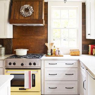 Country Küche in L-Form mit Schrankfronten im Shaker-Stil, weißen Schränken, Quarzwerkstein-Arbeitsplatte, bunten Elektrogeräten, braunem Holzboden und Küchenrückwand in Braun in Cleveland