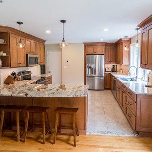 他の地域の中サイズのカントリー風おしゃれなキッチン (アンダーカウンターシンク、シェーカースタイル扉のキャビネット、茶色いキャビネット、御影石カウンター、ベージュキッチンパネル、サブウェイタイルのキッチンパネル、シルバーの調理設備の、磁器タイルの床、ベージュの床、ベージュのキッチンカウンター) の写真