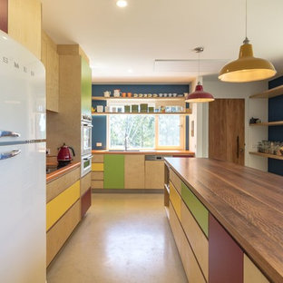 This is an example of a mid-sized contemporary l-shaped eat-in kitchen in Canberra - Queanbeyan with a double-bowl sink, flat-panel cabinets, light wood cabinets, with island, orange benchtop, white appliances and beige floor.