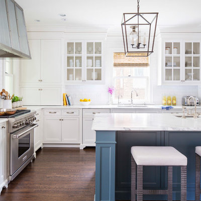 Elegant l-shaped dark wood floor kitchen photo in Minneapolis with an undermount sink, white cabinets, white backsplash, subway tile backsplash, stainless steel appliances, an island, marble countertops and recessed-panel cabinets