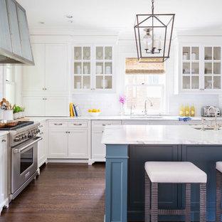 Klassische Küche in L-Form mit Unterbauwaschbecken, Glasfronten, weißen Schränken, Küchenrückwand in Weiß, Rückwand aus Metrofliesen, Küchengeräten aus Edelstahl, dunklem Holzboden, Kücheninsel und Marmor-Arbeitsplatte in Minneapolis