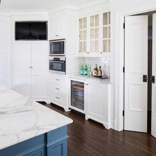 Foto på ett vintage kök, med skåp i shakerstil, vita skåp, marmorbänkskiva, vitt stänkskydd, stänkskydd i tunnelbanekakel, rostfria vitvaror, mörkt trägolv och en köksö