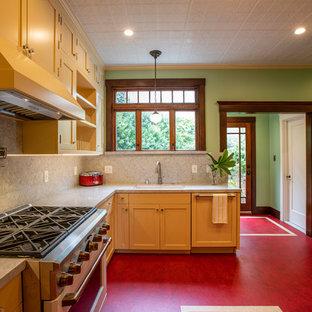 Mittelgroße Urige Küche in U-Form mit Vorratsschrank, Unterbauwaschbecken, Schrankfronten im Shaker-Stil, gelben Schränken, Quarzwerkstein-Arbeitsplatte, Küchenrückwand in Grau, Rückwand aus Marmor, Elektrogeräten mit Frontblende, Linoleum, Kücheninsel, rotem Boden und grauer Arbeitsplatte in San Francisco