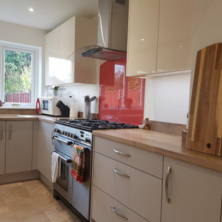This is an example of a small contemporary u-shaped separate kitchen in West Midlands with a double-bowl sink, flat-panel cabinets, beige cabinets, laminate benchtops, orange splashback, glass sheet splashback, black appliances, vinyl floors, no island, brown floor and brown benchtop.