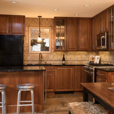 Inspiration for a small craftsman u-shaped terrazzo floor eat-in kitchen remodel in Boston with an undermount sink, raised-panel cabinets, medium tone wood cabinets, granite countertops, beige backsplash, travertine backsplash, stainless steel appliances and a peninsula