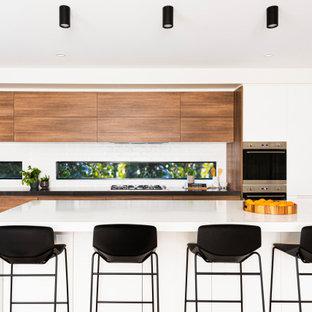 コンテンポラリースタイルのおしゃれなキッチン (アンダーカウンターシンク、フラットパネル扉のキャビネット、中間色木目調キャビネット、ガラスまたは窓のキッチンパネル、シルバーの調理設備の、無垢フローリング、茶色い床、白いキッチンカウンター) の写真