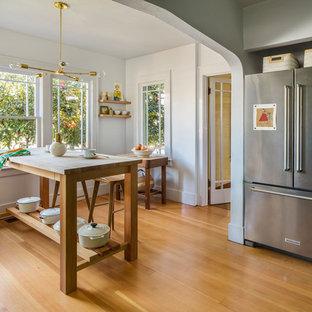 ポートランドの小さいカントリー風おしゃれなキッチン (エプロンフロントシンク、落し込みパネル扉のキャビネット、緑のキャビネット、木材カウンター、グレーのキッチンパネル、ガラスタイルのキッチンパネル、シルバーの調理設備、淡色無垢フローリング、ベージュの床、ベージュのキッチンカウンター) の写真