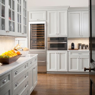 Photo of a classic u-shaped kitchen pantry in New York with recessed-panel cabinets, grey cabinets, marble worktops, beige splashback, stone tiled splashback, stainless steel appliances, medium hardwood flooring, brown floors and grey worktops.