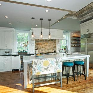 Lantlig inredning av ett stort kök, med vita skåp, vitt stänkskydd, rostfria vitvaror, en köksö, en rustik diskho, släta luckor, bänkskiva i täljsten och mellanmörkt trägolv