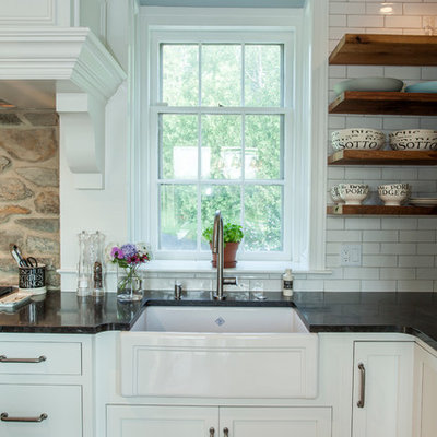 Mid-sized cottage l-shaped medium tone wood floor eat-in kitchen photo in Philadelphia with a farmhouse sink, shaker cabinets, white cabinets, marble countertops, white backsplash, subway tile backsplash, stainless steel appliances and an island