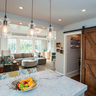 Example of a mid-sized cottage l-shaped medium tone wood floor eat-in kitchen design in Philadelphia with a farmhouse sink, shaker cabinets, white cabinets, marble countertops, white backsplash, subway tile backsplash, stainless steel appliances and an island