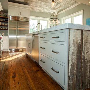 Inspiration for a large country u-shaped light wood floor open concept kitchen remodel in Philadelphia with a farmhouse sink, white cabinets, white backsplash, subway tile backsplash, stainless steel appliances, an island, flat-panel cabinets and soapstone countertops