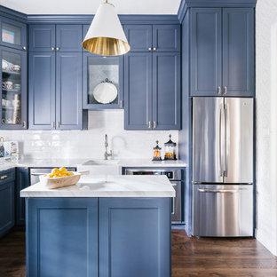 Foto di una cucina a L tradizionale con lavello stile country, ante in stile shaker, ante blu, paraspruzzi bianco, elettrodomestici in acciaio inossidabile, pavimento in legno massello medio, isola, pavimento marrone e top bianco