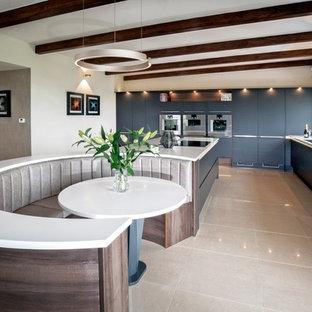 Inspiration för mycket stora moderna vitt l-kök, med släta luckor, blå skåp, rostfria vitvaror, en köksö, beiget golv, en undermonterad diskho och fönster som stänkskydd