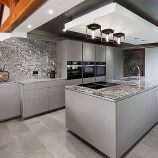 Inspiration for a mid-sized contemporary galley open plan kitchen in Glasgow with an undermount sink, flat-panel cabinets, grey cabinets, granite benchtops, multi-coloured splashback, black appliances, vinyl floors, with island, grey floor, multi-coloured benchtop and wood.