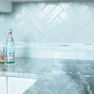 クリーブランドの中くらいのビーチスタイルのおしゃれなキッチン (青いキッチンパネル、インセット扉のキャビネット、白いキャビネット、御影石カウンター、セラミックタイルのキッチンパネル、白い調理設備) の写真