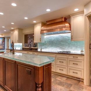 デンバーの中くらいのコンテンポラリースタイルのおしゃれなキッチン (アンダーカウンターシンク、落し込みパネル扉のキャビネット、白いキャビネット、ガラスカウンター、ガラス板のキッチンパネル、トラバーチンの床、青いキッチンパネル、ターコイズのキッチンカウンター) の写真