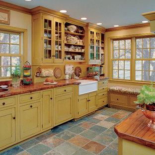 Cette photo montre une petite cuisine parallèle nature fermée avec un évier de ferme, des portes de placard jaunes, un plan de travail en cuivre, une crédence jaune, un électroménager encastrable, un sol en ardoise, aucun îlot, un placard à porte shaker et un plan de travail rouge.