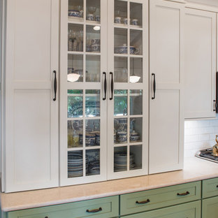 Mid-sized country galley eat-in kitchen in Milwaukee with a farmhouse sink, recessed-panel cabinets, green cabinets, quartzite benchtops, beige splashback, subway tile splashback, stainless steel appliances, light hardwood floors, with island and beige floor.