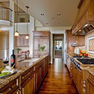 Idées déco pour une cuisine parallèle victorienne avec un plan de travail en granite, un placard avec porte à panneau surélevé, des portes de placard en bois brun, une crédence beige, un électroménager encastrable et un sol marron.