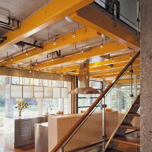 Inspiration för ett industriellt kök, med en köksö, en integrerad diskho, släta luckor, skåp i rostfritt stål, bänkskiva i rostfritt stål, rostfria vitvaror och mellanmörkt trägolv