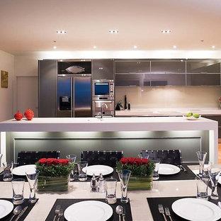 Zweizeilige Moderne Wohnküche mit Küchengeräten aus Edelstahl, flächenbündigen Schrankfronten, grauen Schränken, Mineralwerkstoff-Arbeitsplatte, Küchenrückwand in Beige, Glasrückwand, hellem Holzboden und Kücheninsel in Los Angeles