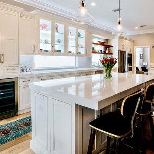 Klassische Wohnküche mit Kassettenfronten, weißen Schränken, Kupfer-Arbeitsplatte, Küchenrückwand in Gelb, Rückwand aus Glasfliesen und zwei Kücheninseln in Sonstige