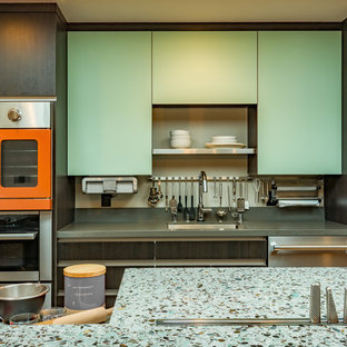 Large contemporary l-shaped open plan kitchen in San Francisco with an undermount sink, flat-panel cabinets, grey cabinets, recycled glass benchtops, coloured appliances, cork floors and with island.
