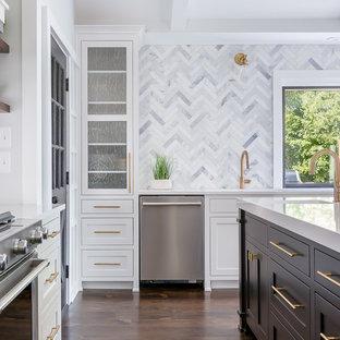 Idées déco pour une grand cuisine américaine classique en L avec un évier encastré, un placard à porte shaker, des portes de placard blanches, un plan de travail en quartz, une crédence grise, une crédence en marbre, un électroménager en acier inoxydable, un sol en bois foncé, un îlot central, un sol marron et un plan de travail blanc.
