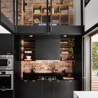 Große Industrial Küche in L-Form mit Vorratsschrank, Unterbauwaschbecken, schwarzen Schränken, Arbeitsplatte aus Holz, Rückwand aus Backstein, Küchengeräten aus Edelstahl, Betonboden und Kücheninsel in Sunshine Coast