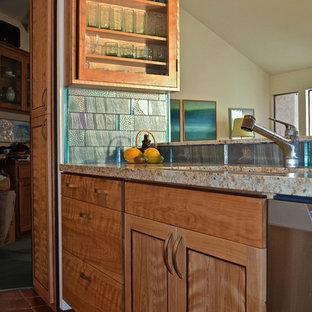 Idéer för mellanstora amerikanska kök, med granitbänkskiva, blått stänkskydd, rostfria vitvaror, klinkergolv i keramik, en undermonterad diskho, släta luckor, skåp i mellenmörkt trä, stänkskydd i glaskakel och en halv köksö