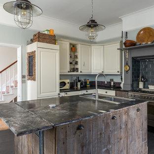 サセックスの中サイズのインダストリアルスタイルのおしゃれなキッチン (ダブルシンク、レイズドパネル扉のキャビネット、白いキャビネット、黒いキッチンパネル、サブウェイタイルのキッチンパネル、シルバーの調理設備の、黒い床、黒いキッチンカウンター、濃色無垢フローリング) の写真