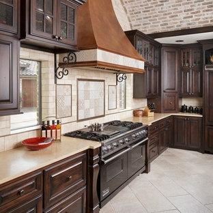 Inspiration för stora medelhavsstil kök, med luckor med upphöjd panel, skåp i mörkt trä, granitbänkskiva, beige stänkskydd, stänkskydd i porslinskakel, svarta vitvaror, klinkergolv i porslin och beiget golv