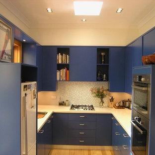 シドニーのヴィクトリアン調のおしゃれなコの字型キッチン (アンダーカウンターシンク、フラットパネル扉のキャビネット、青いキャビネット、人工大理石カウンター、モザイクタイルのキッチンパネル、シルバーの調理設備、淡色無垢フローリング、マルチカラーの床、白いキッチンカウンター) の写真