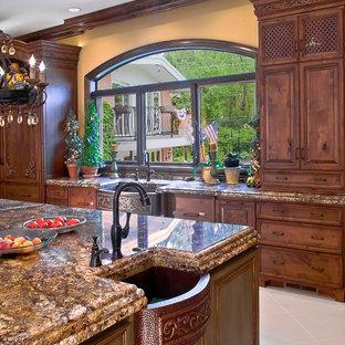 Medium sized mediterranean galley kitchen/diner in Chicago with a belfast sink, raised-panel cabinets, dark wood cabinets, granite worktops, porcelain flooring, an island and white floors.